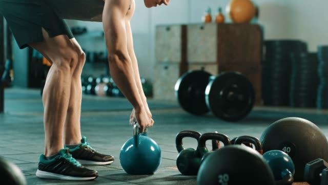 man doing exercise with kettlebell in gym - giria filmów i materiałów b-roll