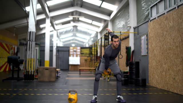 man doing exercises with kettlebell - giria filmów i materiałów b-roll