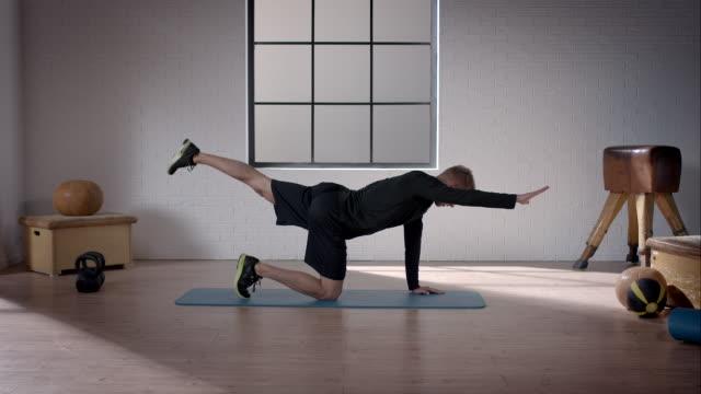 uomo fare suo allenamento in palestra (a carponi posizione in diagonale - metodo pilates video stock e b–roll