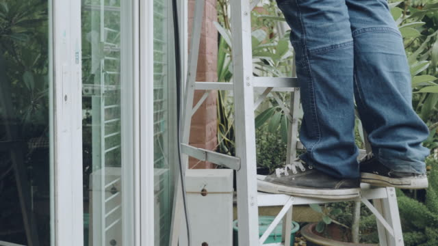 stockvideo's en b-roll-footage met een man doet onderhoud woning - ladder