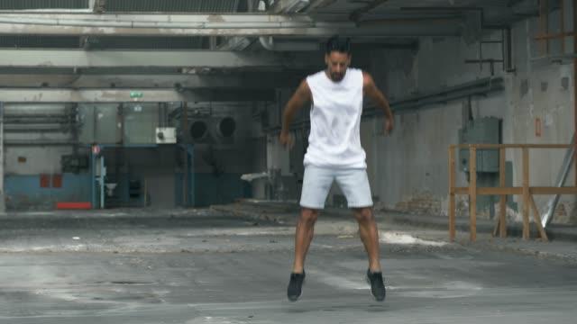 vídeos de stock e filmes b-roll de man doing jumping exercises in an abandoned warehouse - agachar se