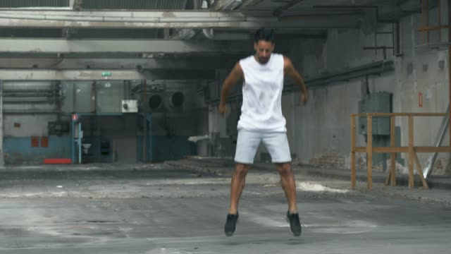 man doing jumping exercises in an abandoned warehouse - rozgrzewka filmów i materiałów b-roll
