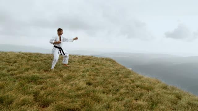 vídeos de stock, filmes e b-roll de ws zi zo man doing karate at edge of mountain / vipava, nature park nanos, slovenia - artes marciais