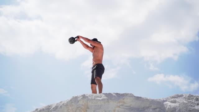 Bидео Man doing kettlebell workout