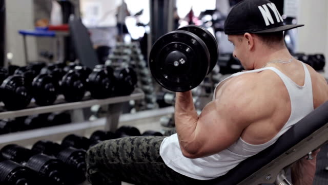 Man doing lift-ups, holding heavy dumbbells in hands, workout for arm muscles - vídeo