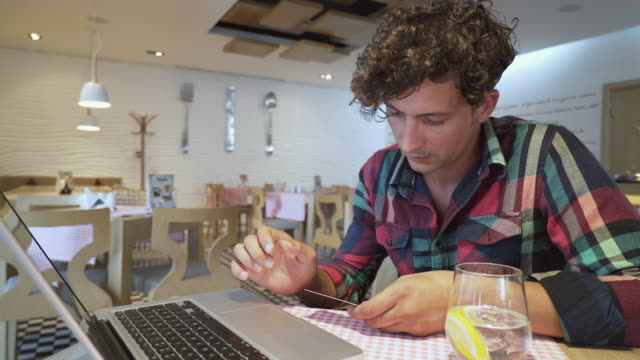 Man doing online payments. Man doing online payments. He is in a restaurant paying some bills or doing online shopping. gold card stock videos & royalty-free footage