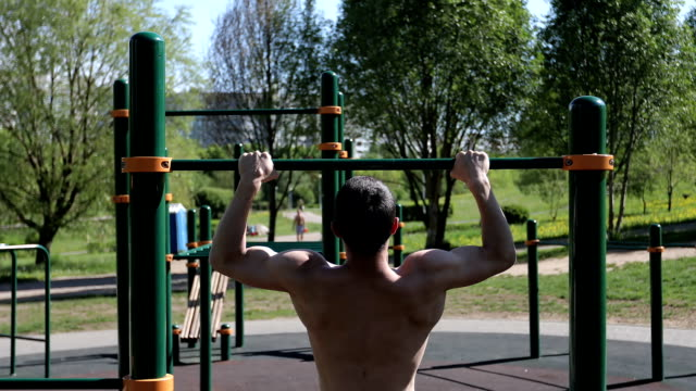 Man doing pull ups outdoors. video