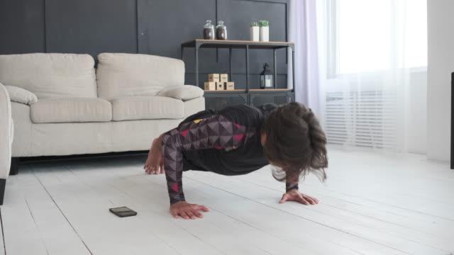 man doing push ups while using mobile phone at home - pantaloncini video stock e b–roll