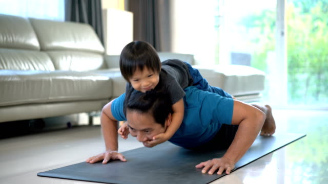 man doing push ups with happy baby on his back at home. - genitori video stock e b–roll