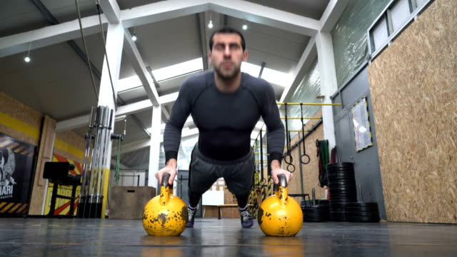 man doing push ups with kettle bell on cross fitness training - working out in a gym - miroslav mitic stock videos and b-roll footage