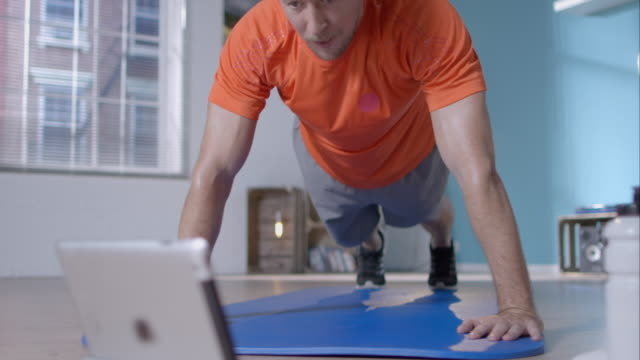 Man doing pushups for his workout A man is doing his workout at home. He watches some instructions. His current exercise is pushups. push ups stock videos & royalty-free footage