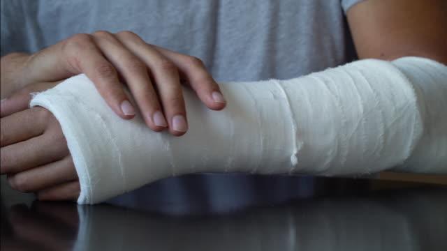 vídeos de stock, filmes e b-roll de homem fazendo auto massagem para braço quebrado enrolado em gesso fundido - punho