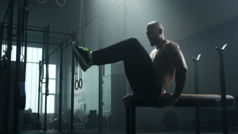 Man doing sit-ups on bench and train his abdominal muscles Young man doing sit-ups on bench and train his abdominal muscles in gym concentration stock videos & royalty-free footage