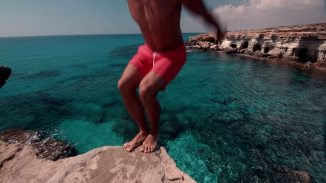 man doing somersault jumping off cliff and diving into sea - tuffarsi video stock e b–roll