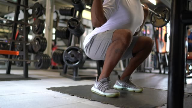 vídeos de stock e filmes b-roll de man doing squat exercises in gym - roupa desportiva