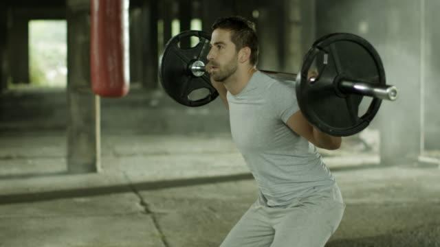 vídeos de stock e filmes b-roll de homem dando squats - agachar se