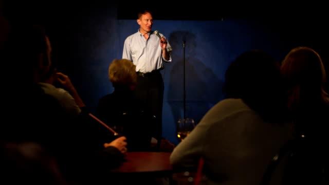 man doing stand up comedy gets an applause - 表演 個影片檔及 b 捲影像