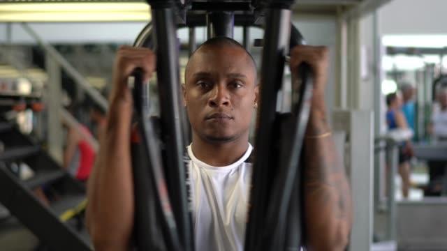 stockvideo's en b-roll-footage met mens die oefening van de krachttraining in gymnastiek doet - fitnessleraar