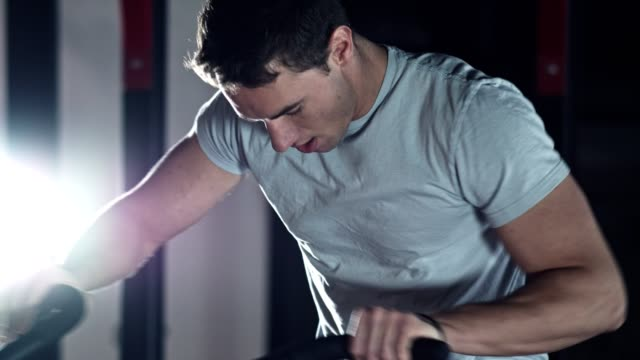 Man doing total body workout on air bike An athletic young man is exercising on air bike in the gym. exercise bike stock videos & royalty-free footage