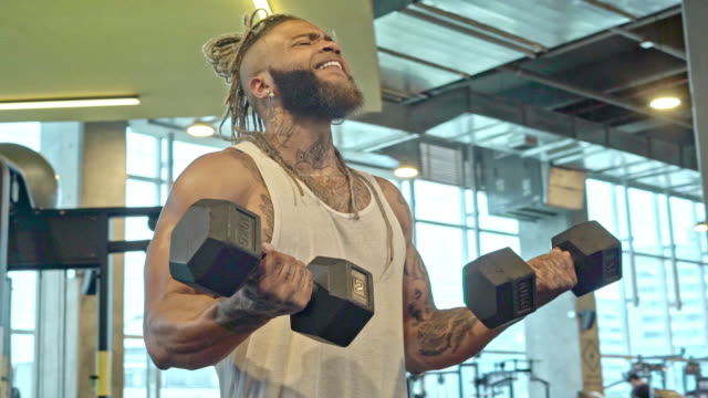 Man doing weights in a gym Afro-Colombian ethnic man doing weights in a gym with an effortless face. He is dressed in sportswear and has braids in his hair. military lifestyle stock videos & royalty-free footage