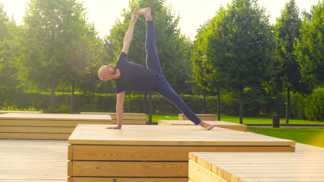 a man doing yoga exercises in the park - flessibilità video stock e b–roll