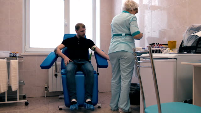 Man donates blood in the doctor's office video