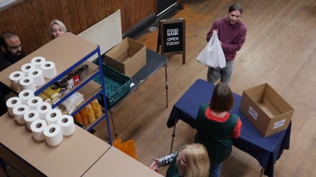 vídeos y material grabado en eventos de stock de 4k antena: hombre donar bolsa llena de alimentos / comida a un banco de alimentos - food drive