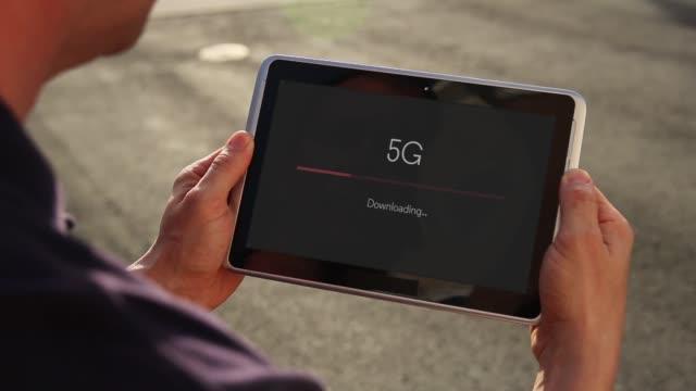 vídeos y material grabado en eventos de stock de hombre descargar video sobre 5g en una tablet pc - descargar internet