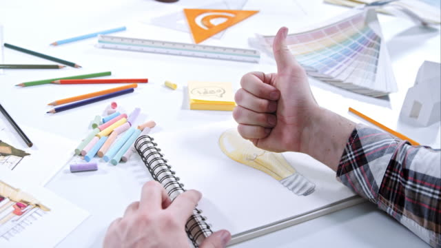 Man drawing light bulb and doing thumb up after finishing video