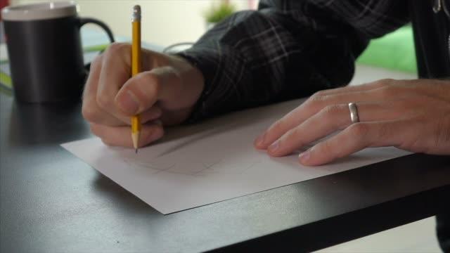 vídeos de stock e filmes b-roll de man drawing with pencil - amarrotado
