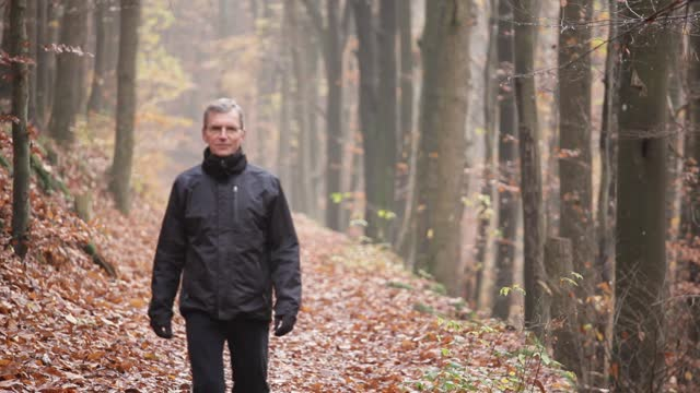 Man dressed in black walking alone in a forest or park in fall or winter - selective focus