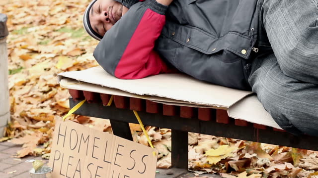 Man dressed in old clothes sleeping on bench in park with homeless help sign video