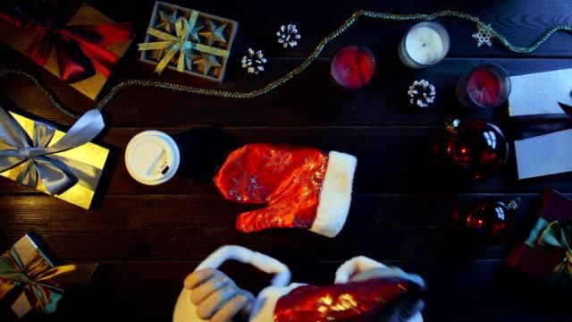 クリスマス木製テーブル、ショットをトップダウンでサンタ クロース スーツ ドリンク コーヒーに身を包んだ男 ビデオ