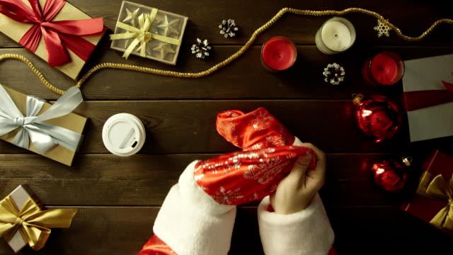 新年木製テーブル、ショットをトップダウンでサンタ クロース スーツ ドリンク コーヒーに身を包んだ男 ビデオ