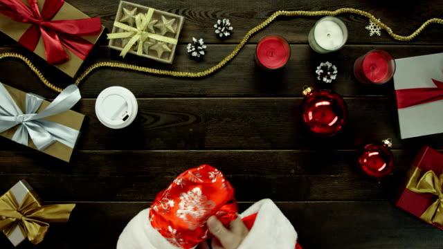 クリスマスの木製テーブル、ショットをトップダウンでサンタ クロース スーツ ドリンク コーヒーに身を包んだ男 ビデオ