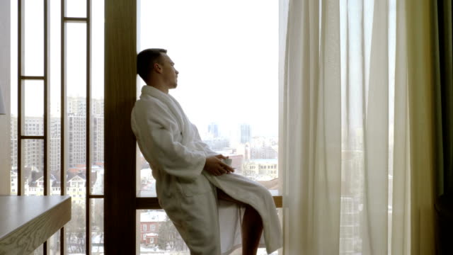 Man dressed in white bathrobe drinking coffee, looking out of window at home. 4K