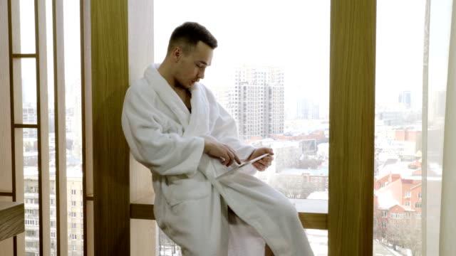 vidéos et rushes de homme rectifié dans le peignoir blanc s'asseyant sur le rebord de fenêtre, utilisant l'ordinateur de tablette. 4k - peignoir