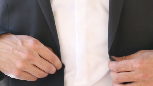 Man dressing upand buttoning jacket video