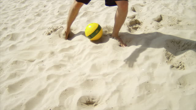 Man dribbles a soccer ball past defenders on sand. video