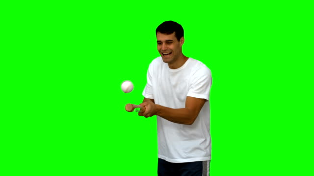 Man dribbling with a baseball on green screen video