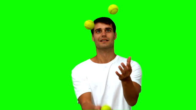 Man dribbling with tennis balls on green screen video