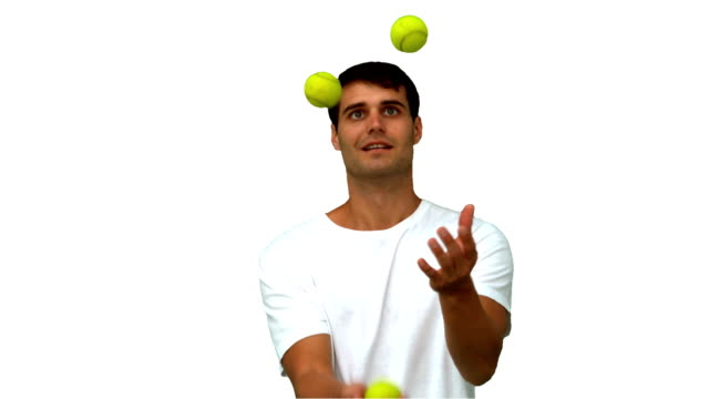 Man dribbling with tennis balls on white screen video