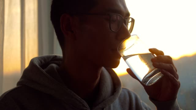 man drinking a cup of water by window in the morning - acqua potabile video stock e b–roll