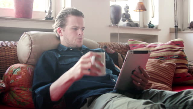 Man drinking coffee and reading on his tablet
