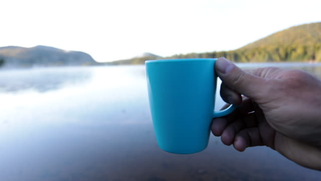 Man Drinking Coffee by the Lake in Camping in Autumn