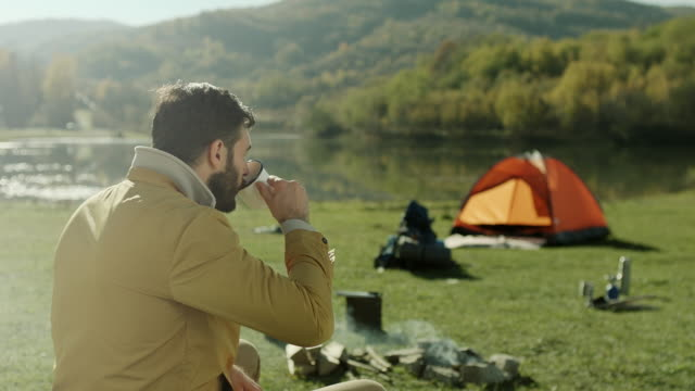 man drinking coffee by the lake - camping stock videos & royalty-free footage