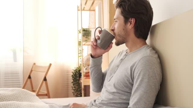 ベッドでコーヒーを飲む男 - マグカップ点の映像素材/bロール