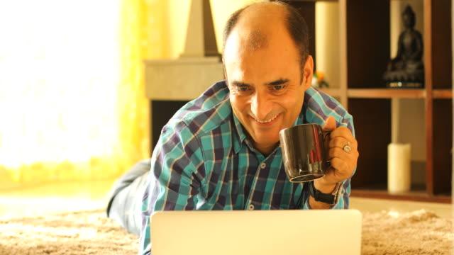 Hombre de beber café durante el uso del ordenador portátil - vídeo