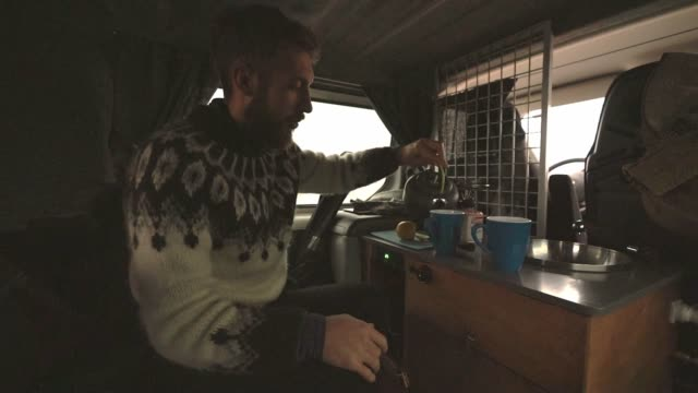Man drinking tea in camper van Young Caucasian man drinking  tea in camper van rv interior stock videos & royalty-free footage
