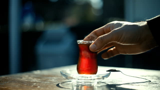 Man drinking Turkish tea with special cup on a sidewalk tea house table with unrecognizable blurry people on the background video